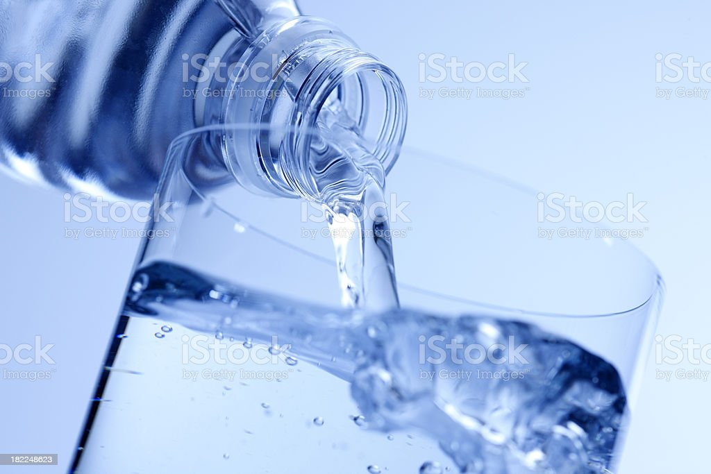 Water from bottle being poured into a glass stock photo