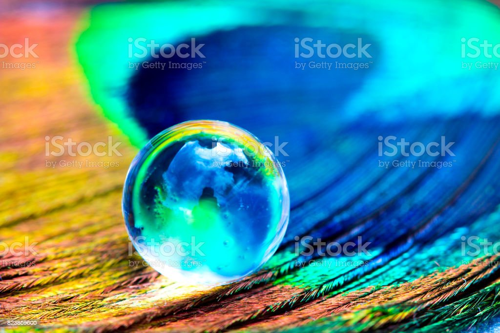 Water gel ball at peacock feathers. Beautiful transfusion of light and colors in the middle of the hydrogel. stock photo