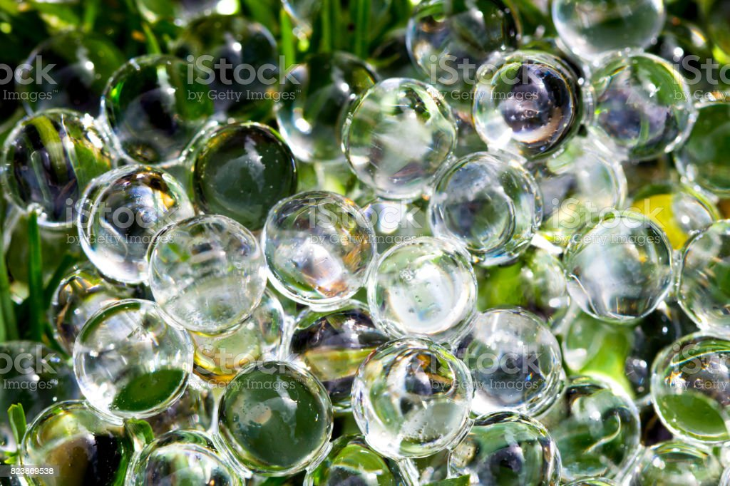 Water gel ball on green fresh grass. Hydrogel with beautiful transfusion of light. stock photo