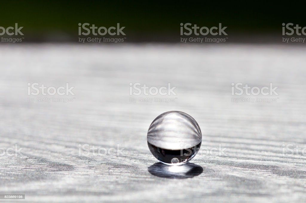 Water gel ball on wood silver texture. Hydrogel with beautiful transfusion of light. stock photo