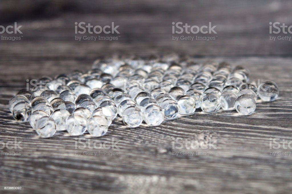 Water gel balls on wood silver texture. Hydrogel with beautiful transfusion of light. stock photo