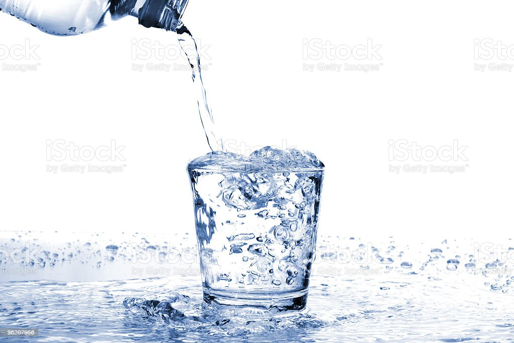 Water glass overflowing from water pouring from bottle royalty-free stock photo