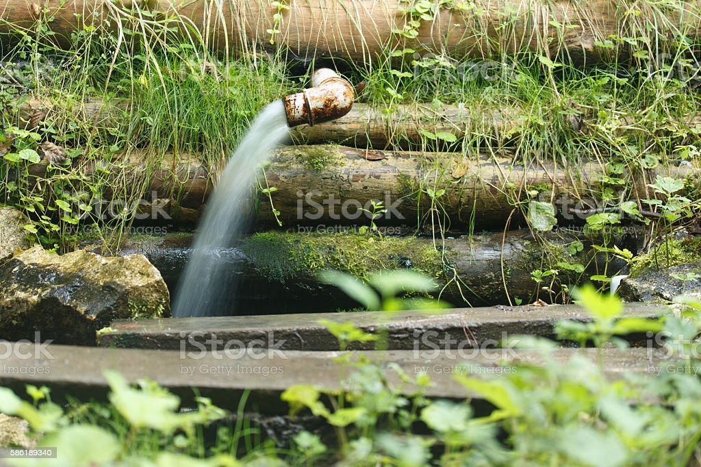 Water gushes from a metal pipe stock photo