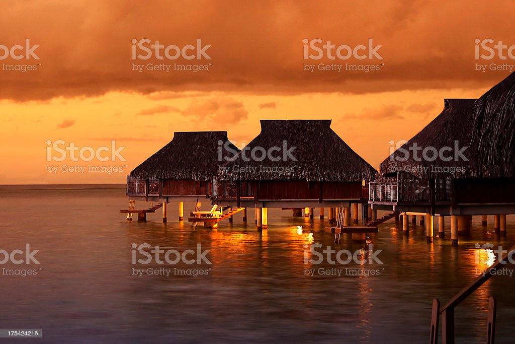 Tropical Tahiti bungalows at sunset