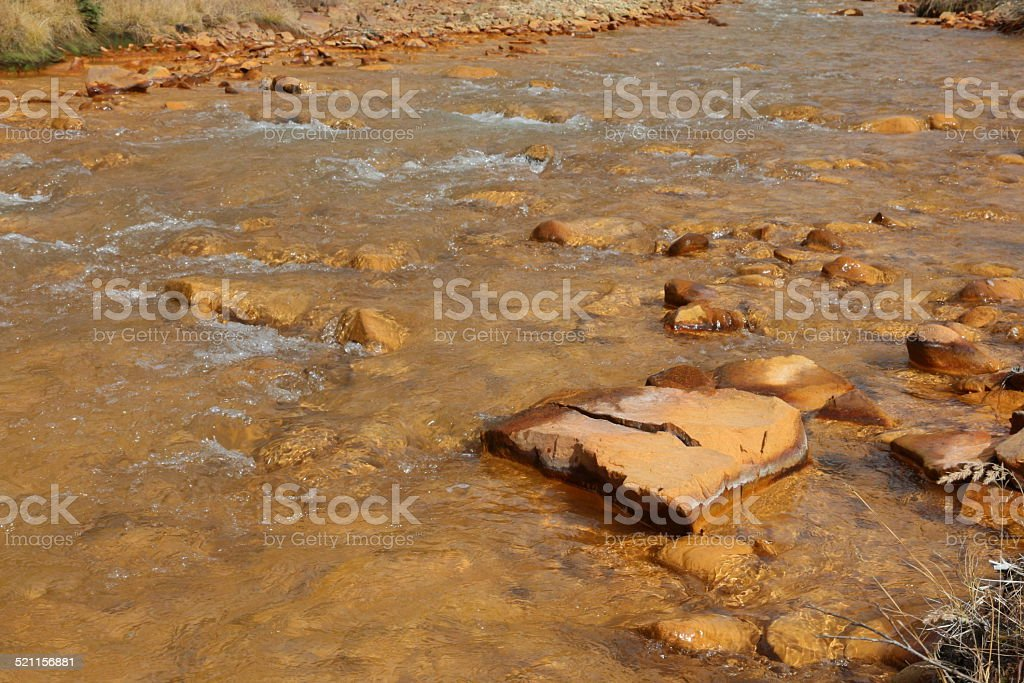 Water in a polluted orange stream in Colorado stock photo