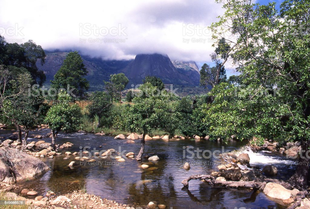 Water in stream flowing from Mulanje Massif in distance southern Malawi Africa stock photo