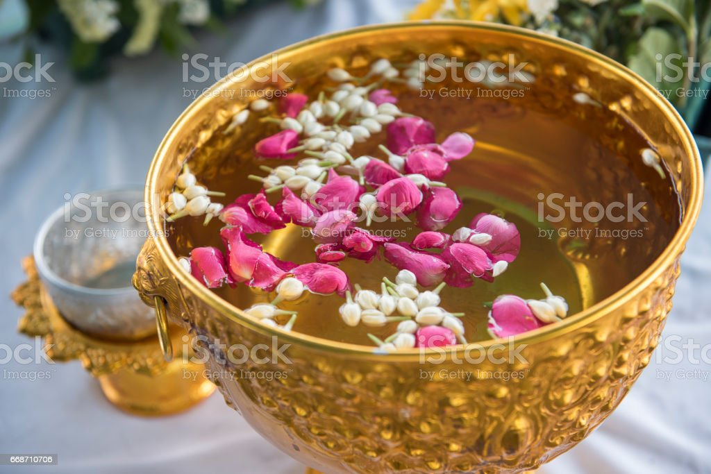 Water in water dipper with colorful flowers pedestal stock photo