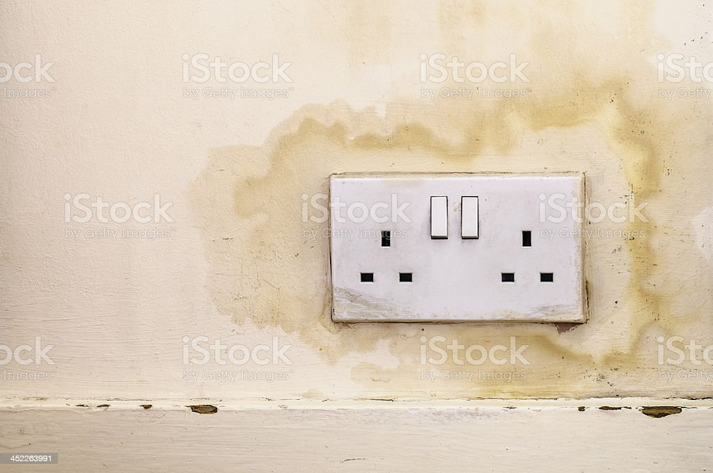 Water Infiltrates Through Wall Around British Electrical Plug Socket stock photo