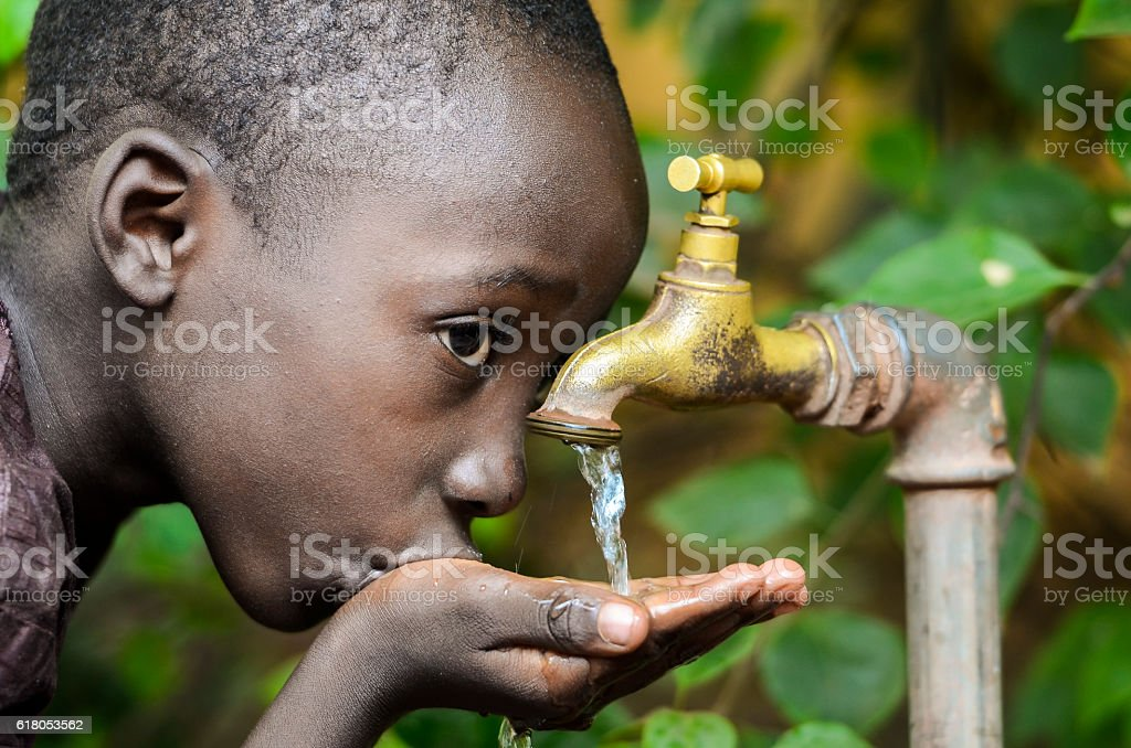 Water is Life! African Baby Boy Drinking Water (Drought Symbol) stock photo