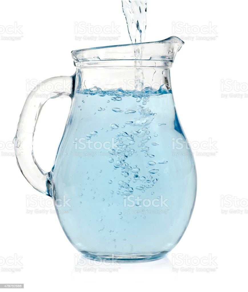 Water is pouring into a pitcher stock photo