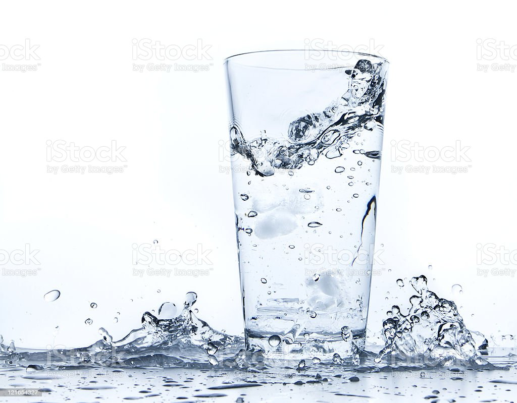 Water is splashing on and around a tall clear glass cup stock photo