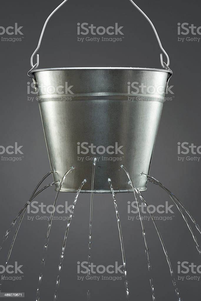 Water leaking from bucket stock photo
