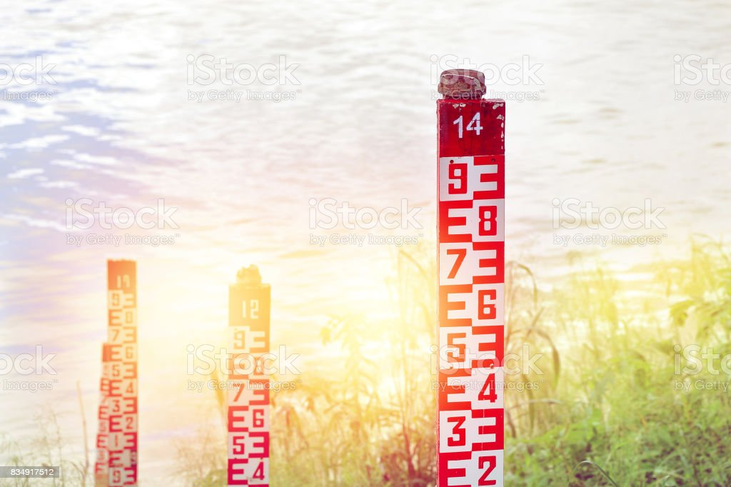 water level marker with numbers at a river in sunlight. stock photo