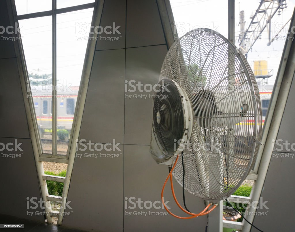 Water misting fan in a train station helps people to stock photo