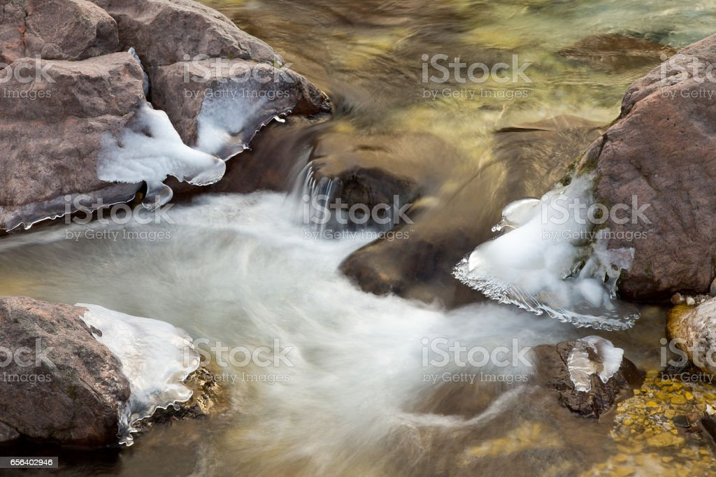 Water motion - Ice on frozen rocks on River stock photo