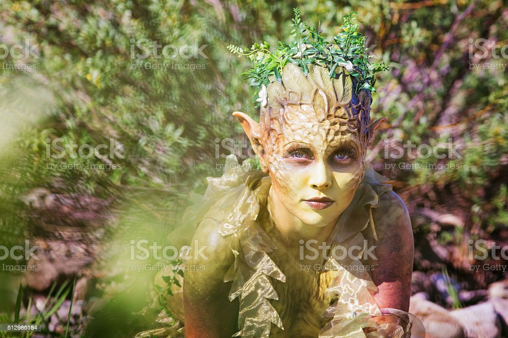 Water Nymph portrait emerging from bushes stock photo