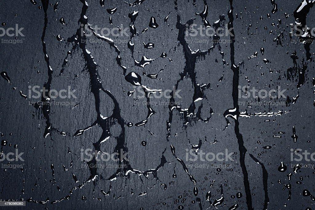 Water on dark stone surface stock photo