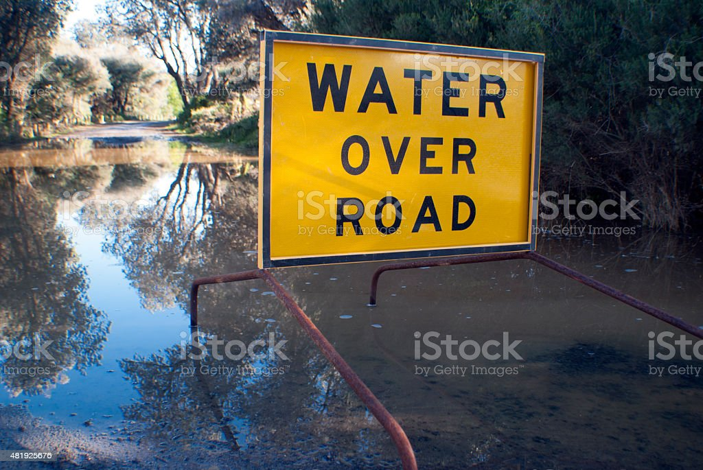 water over road sign stock photo