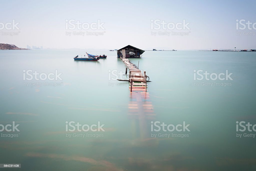 Water overflow on a broken wooden bridge and a hut stock photo