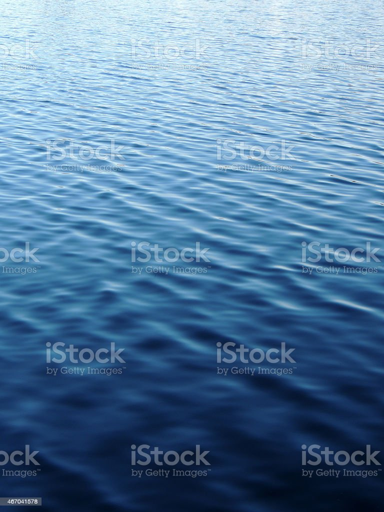 Water peacefully rippling during the day stock photo