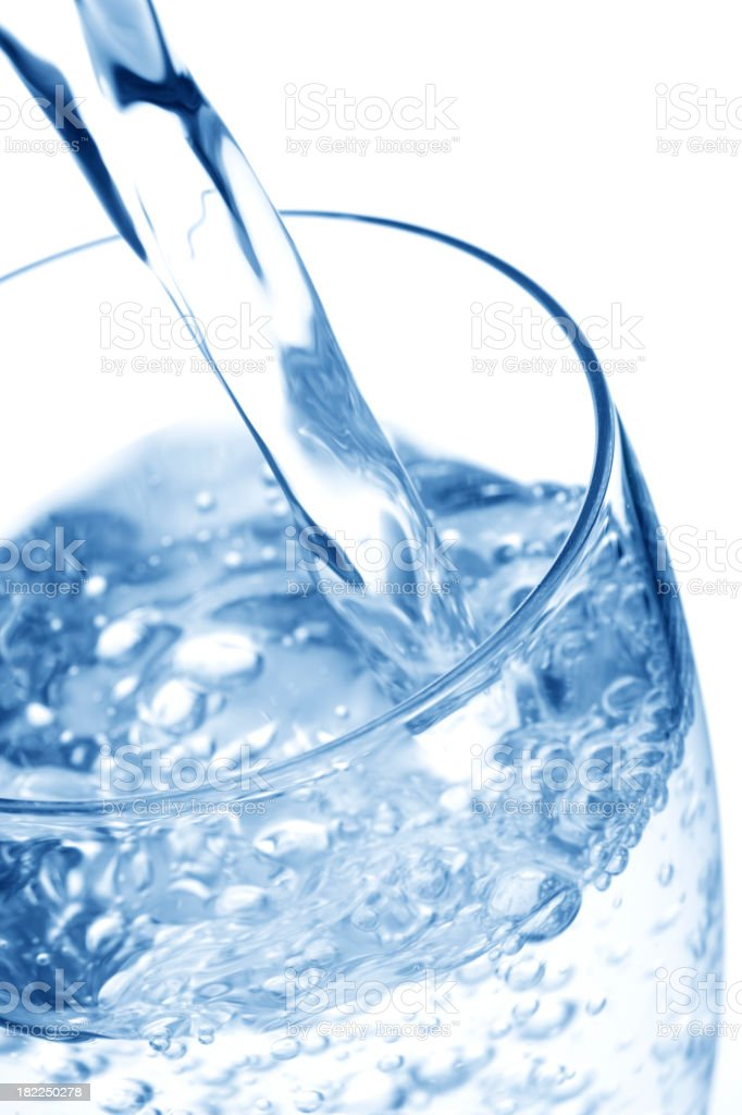 Water peing poured into a glass against white background royalty-free stock photo