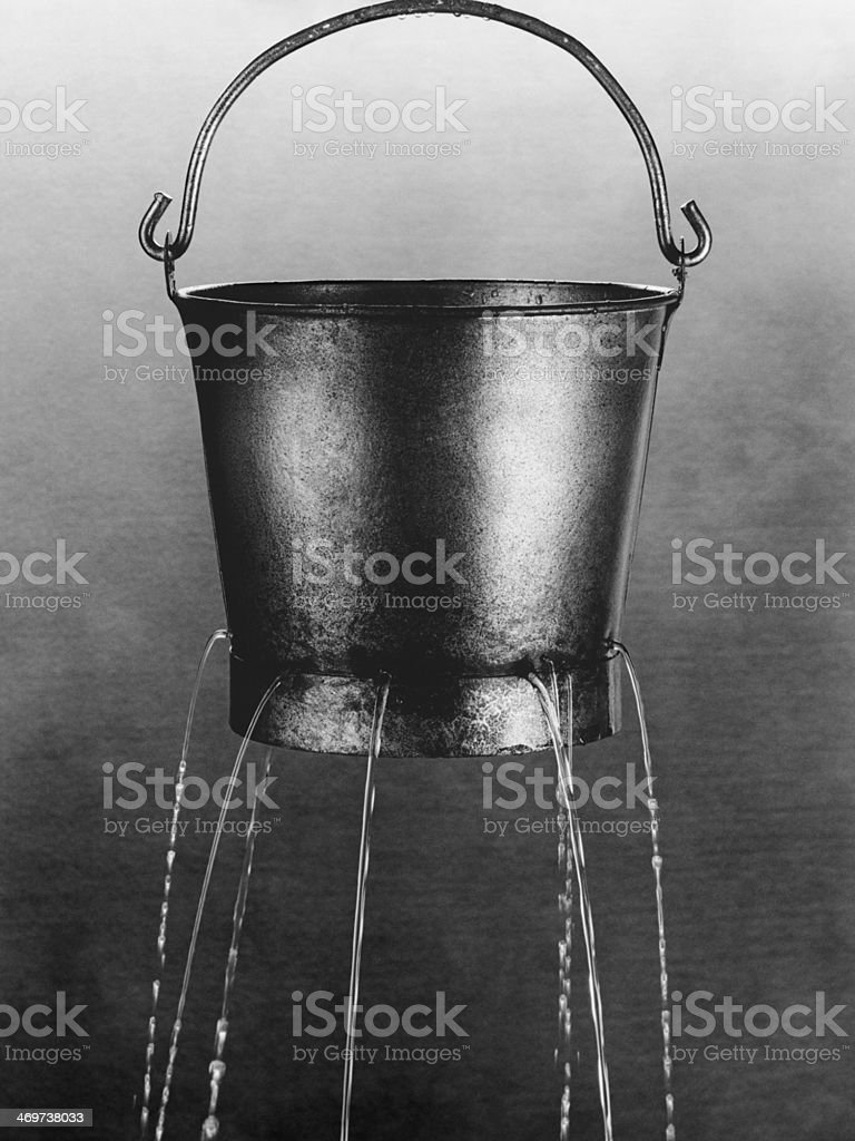Water poring through holes in bucket stock photo