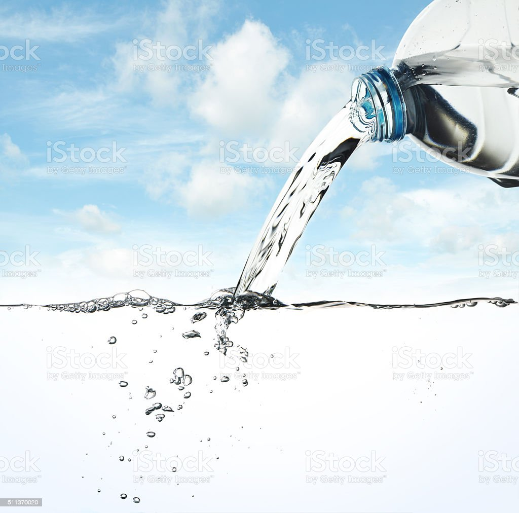 Water pour from water bottle on sky background stock photo