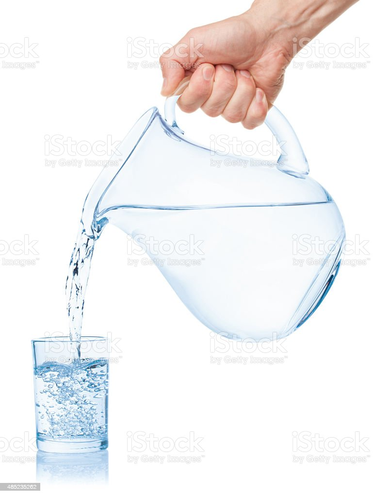 Water poured from the pitcher into a glass. stock photo