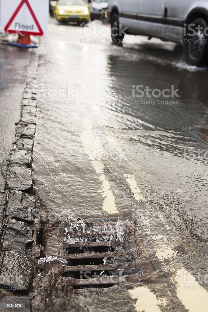 Water Pouring Down Drain On Flooded Road royalty-free stock photo