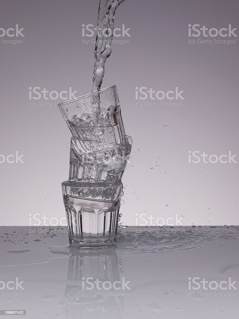 Water pouring into stacked glasses royalty-free stock photo