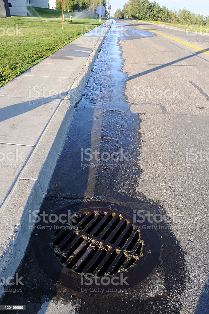 Water Pouring into Street Storm Drain stock photo