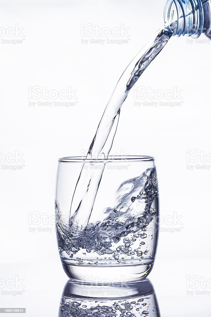 Water pouring into the glass on white stock photo