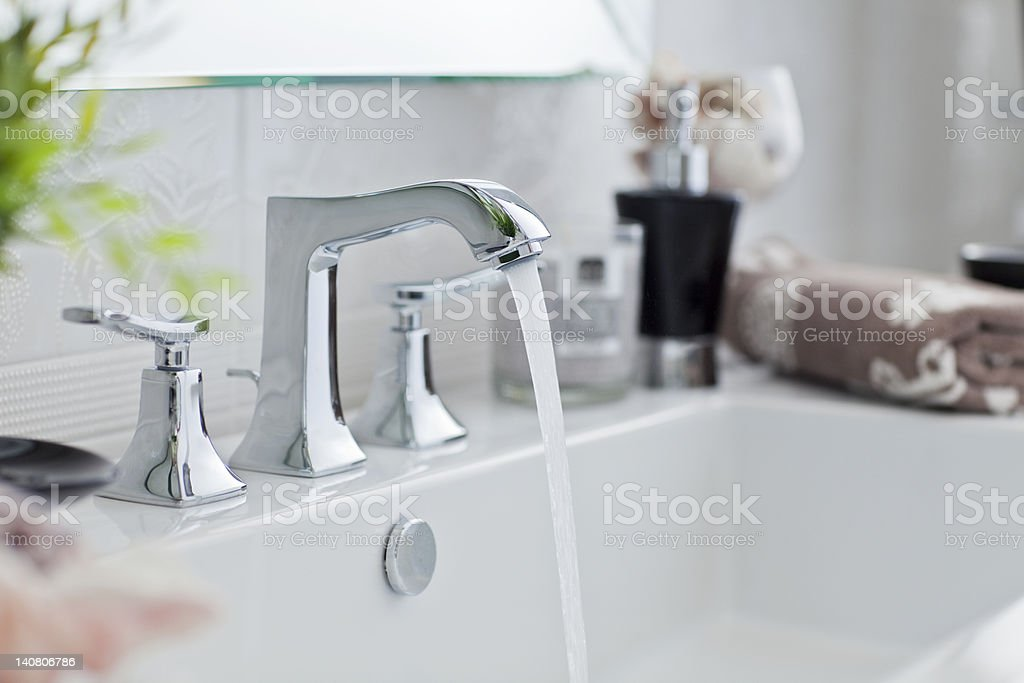 Water pouring out of modern bathroom faucet stock photo
