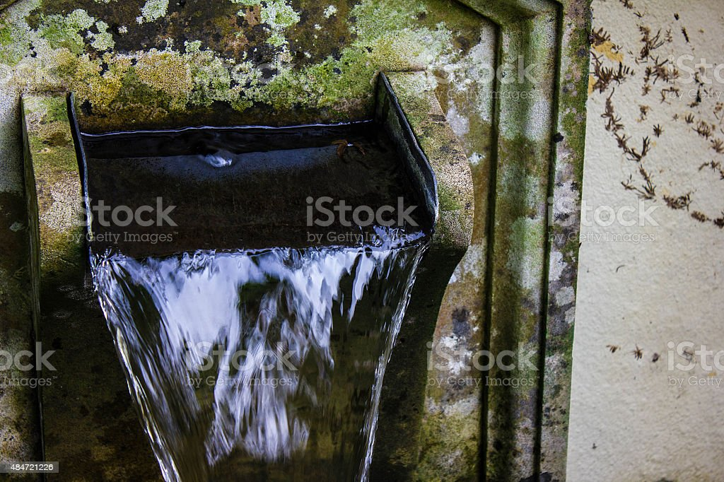Water pours from old stone wall fountain. stock photo