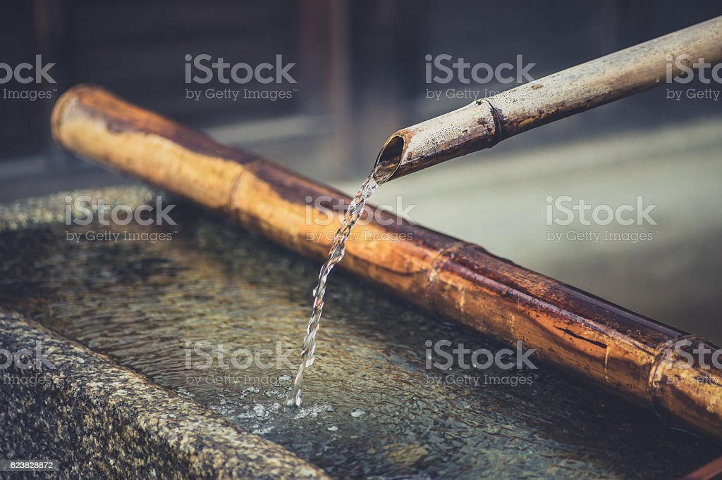 Water Rinse with Bamboo Pipe in Stone Tub at Japan stock photo
