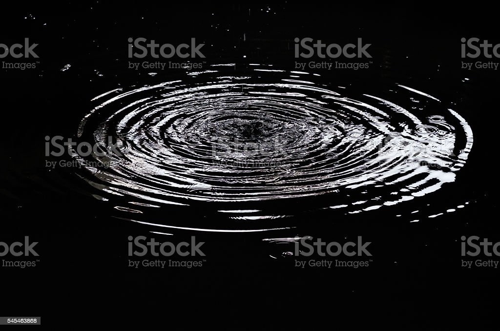 Water ripples from a drop of water in the dark. stock photo