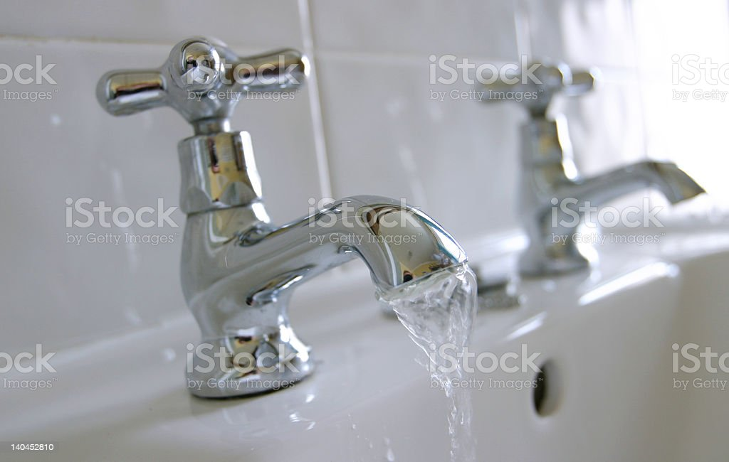 Water running out of a silver faucet on a white sink stock photo