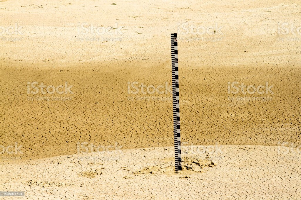 Water scale inside empty dam with mudcrack stock photo