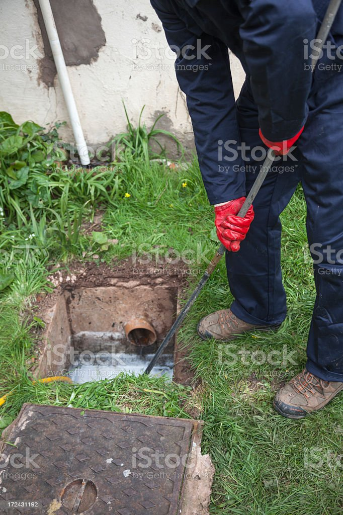 Water service worker stopping a leak on a valve box royalty-free stock photo