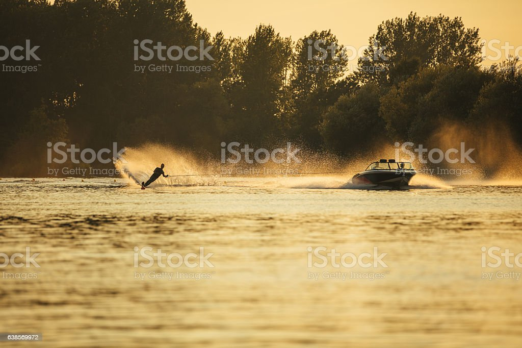 Water skiing on lake behind a boat stock photo