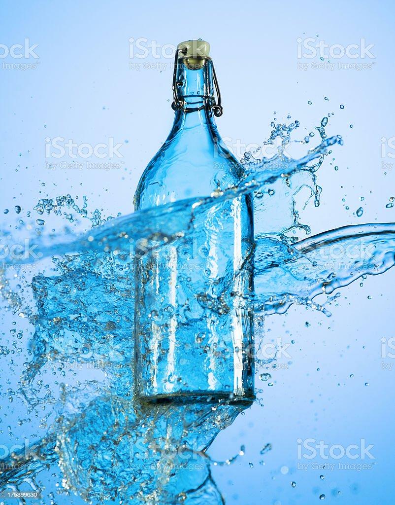 Water Splash on a Bottle. Blue background. stock photo