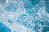Water splashes, waves, drops at blue water background