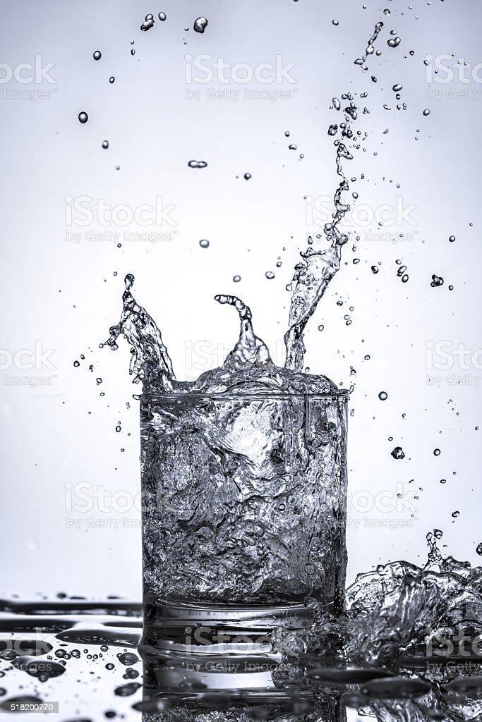 Water splashing into glass stock photo