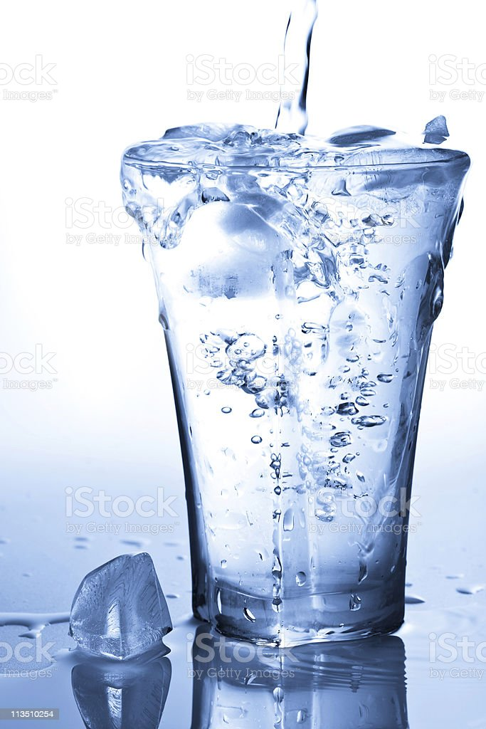 water splashing into glass with ice cubes royalty-free stock photo