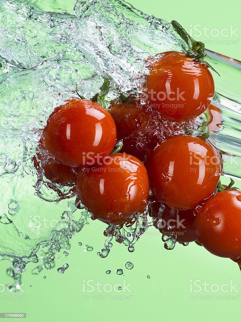 Water Splashing on Cherry Tomatoes. Green Background stock photo