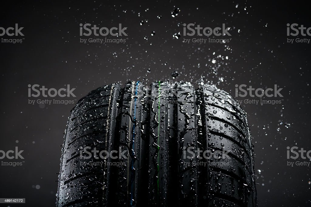 Water splashing on tire during the rain stock photo