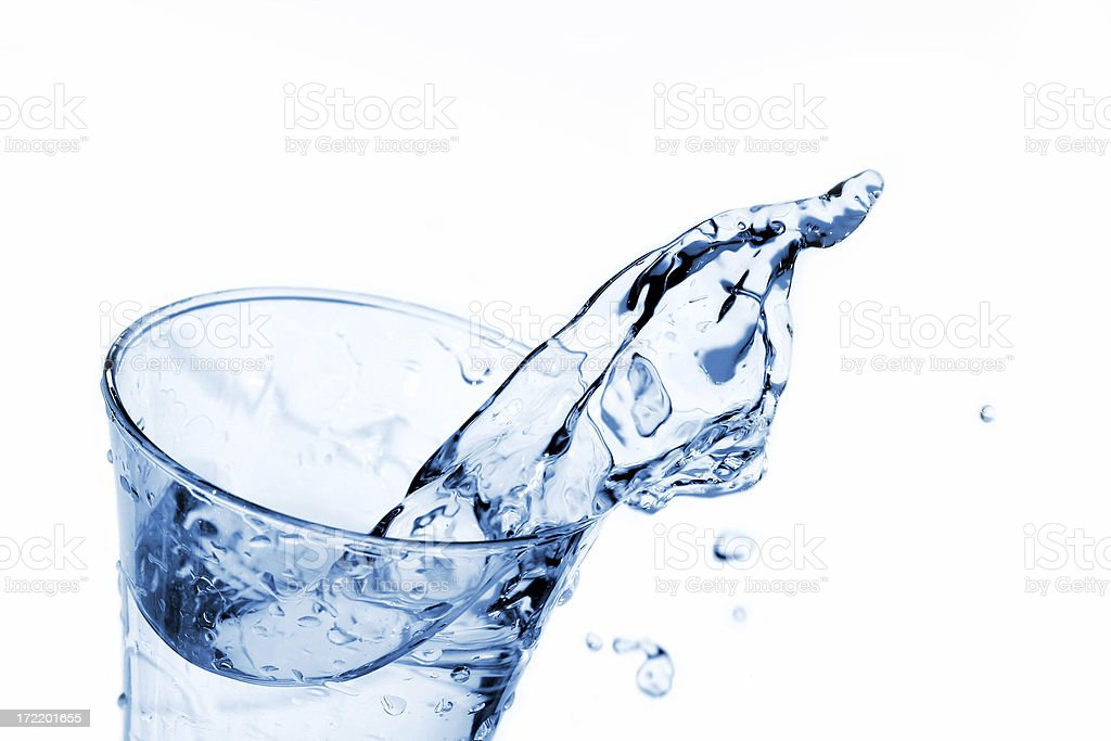 Water splashing out the top of a clear glass stock photo