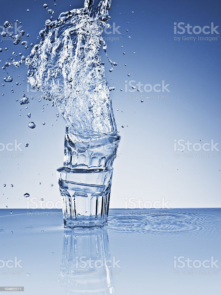 Water splashing over stacked glasses stock photo