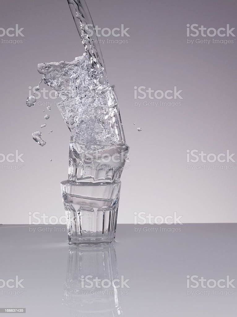 Water splashing over stacked glasses royalty-free stock photo
