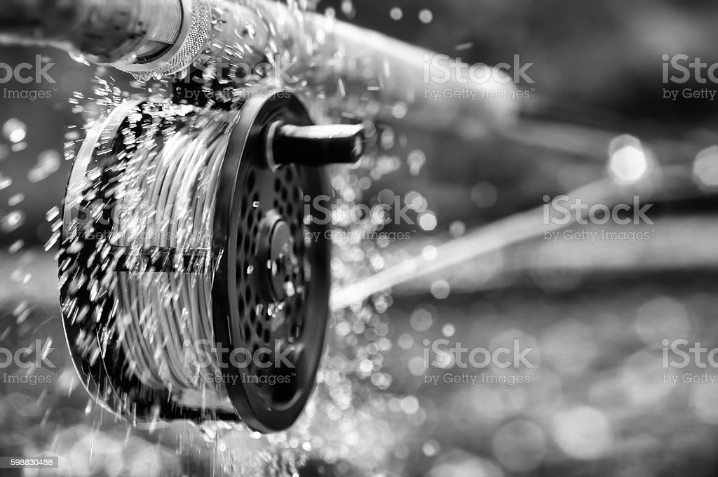 Water spraying form spinning fly-fishing reel stock photo